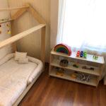 habitacion montessori cama y mueble medio de tres estantes